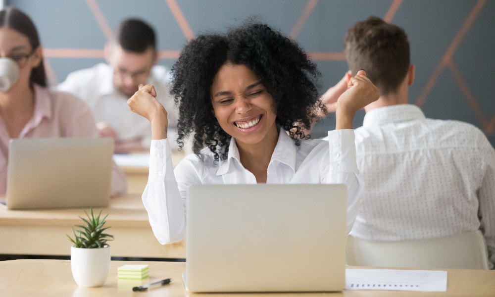 an employee at desk with high employee satisfaction
